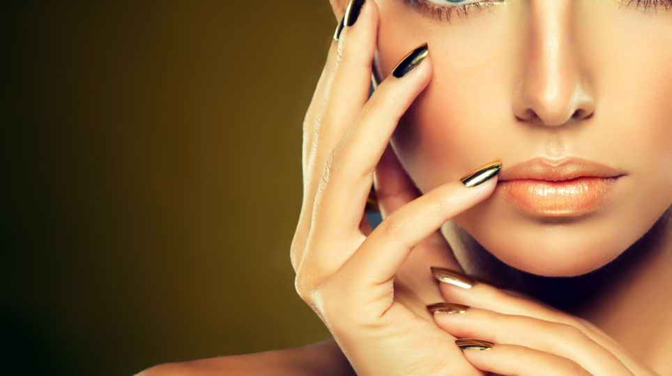 Golden make up, bright gilded manicure and elegant gesture. Portrait of attractive woman model.