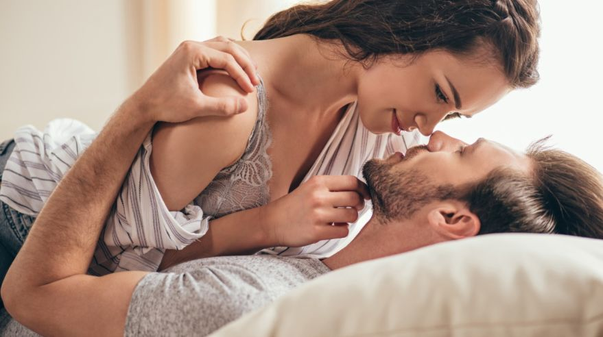 Close-up portrait of beautiful sensual young couple hugging while lying on bed