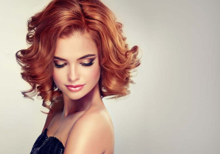 Beautiful model brunette with middle length curled hair and bright make up.