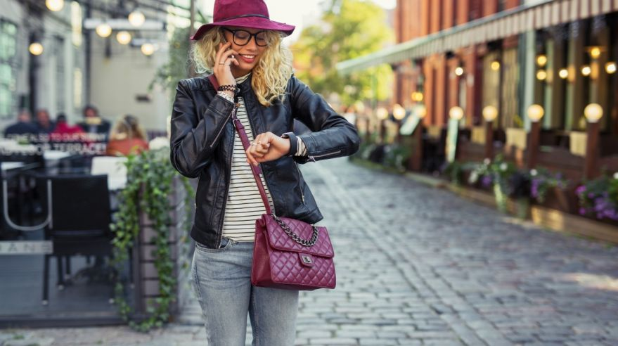 Hipster woman looking at her smartwatch and talking on cellphone