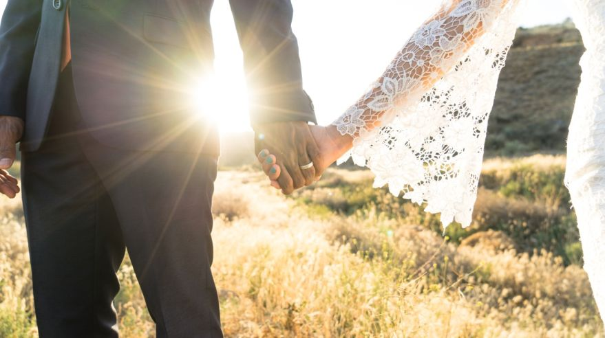 Interracial couple holding hands at wedding