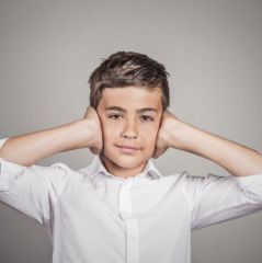 teenager boy covering ears with hands, doesn't want to hear loud noise