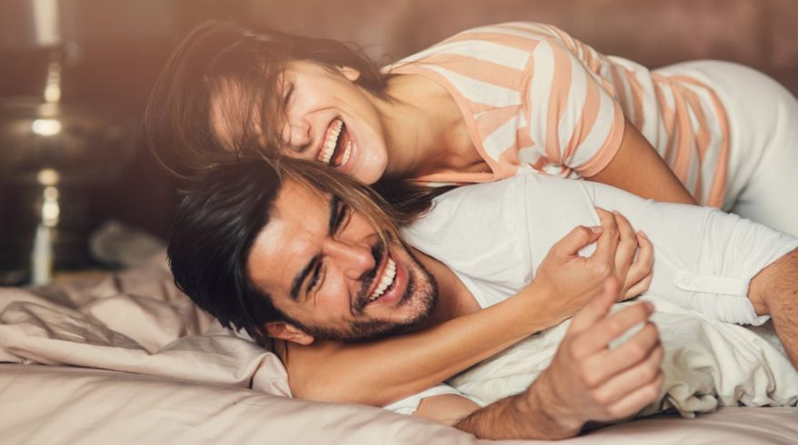 Happy young couple in bed