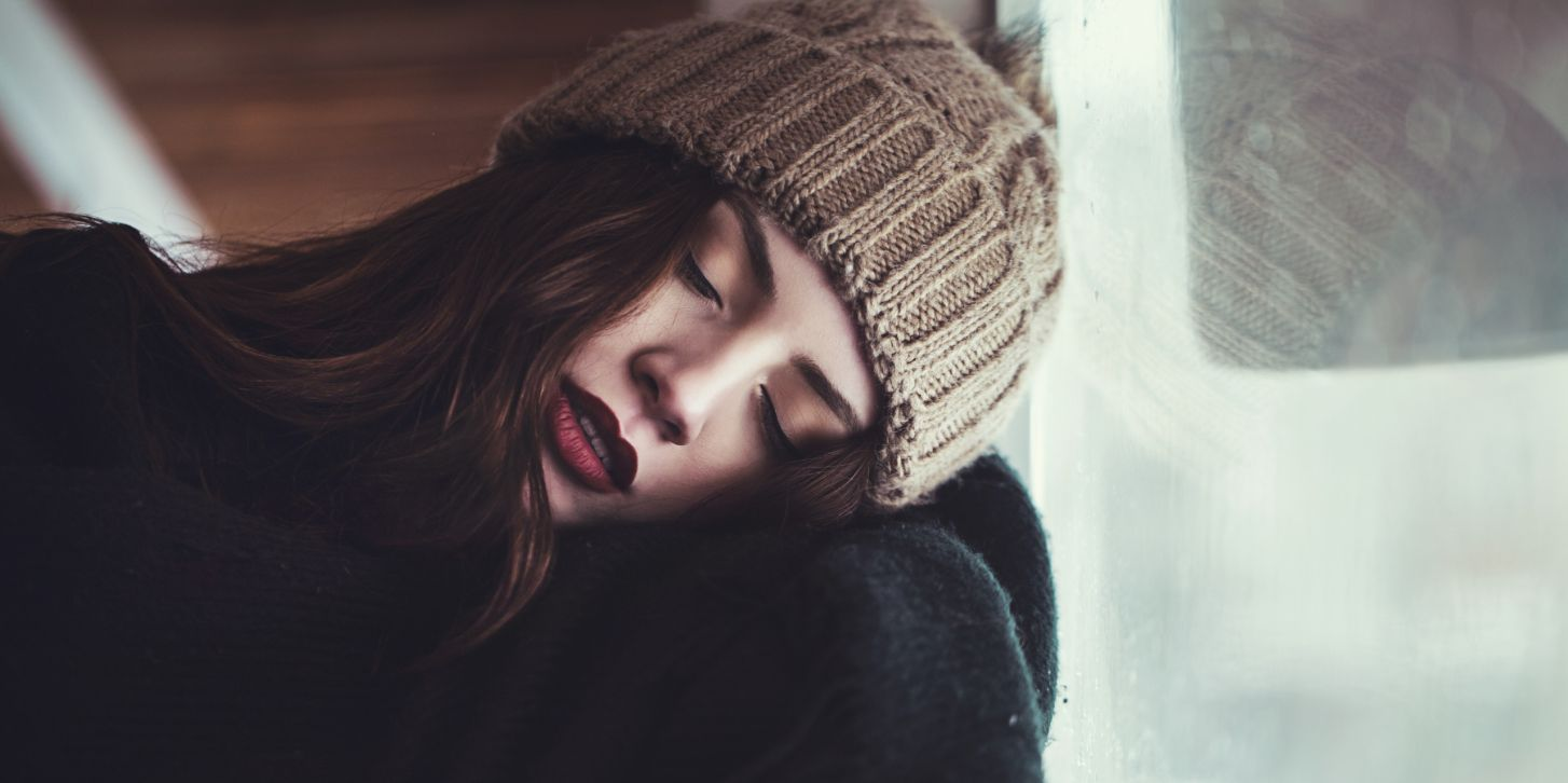 young woman sleeping infront of window