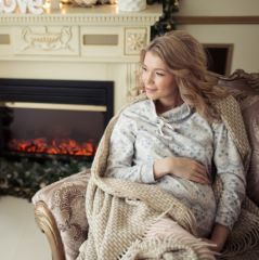 Beautiful Pregnant Woman In A Chair Near The Christmas Tree.