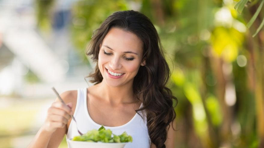 Pretty brunette eating bowl of salad